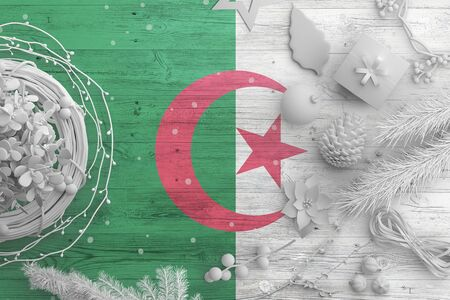 Algeria flag on wooden table with snow objects. Christmas and new year background, celebration national concept with white decor.