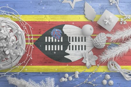 Swaziland flag on wooden table with snow objects. Christmas and new year background, celebration national concept with white decor.