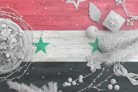 Syria flag on wooden table with snow objects. Christmas and new year background, celebration national concept with white decor.