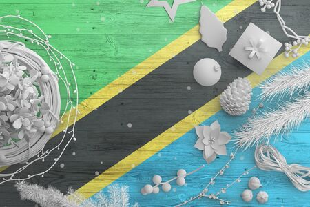 Tanzania flag on wooden table with snow objects. Christmas and new year background, celebration national concept with white decor.