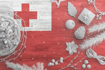 Tonga flag on wooden table with snow objects. Christmas and new year background, celebration national concept with white decor.