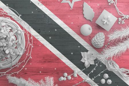 Trinidad And Tobago flag on wooden table with snow objects. Christmas and new year background, celebration national concept with white decor.