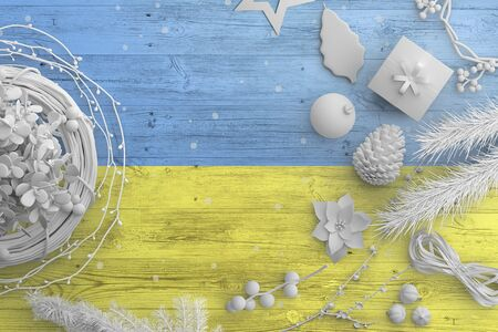 Ukraine flag on wooden table with snow objects. Christmas and new year background, celebration national concept with white decor.