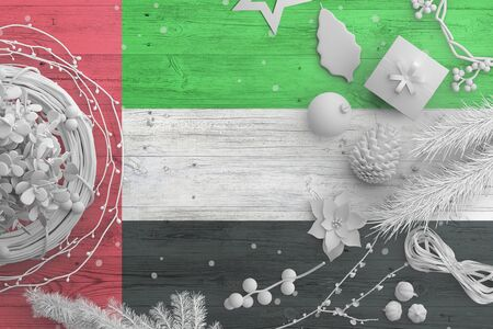 United Arab Emirates flag on wooden table with snow objects. Christmas and new year background, celebration national concept with white decor. 스톡 콘텐츠