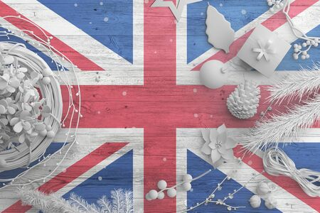 United Kingdom flag on wooden table with snow objects. Christmas and new year background, celebration national concept with white decor.