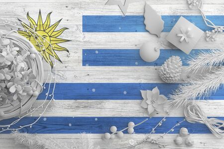 Uruguay flag on wooden table with snow objects. Christmas and new year background, celebration national concept with white decor. Foto de archivo