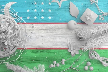 Uzbekistan flag on wooden table with snow objects. Christmas and new year background, celebration national concept with white decor. Foto de archivo