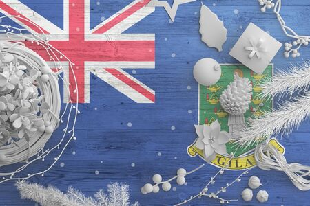 British Virgin Islands flag on wooden table with snow objects. Christmas and new year background, celebration national concept with white decor.