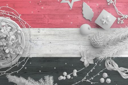 Yemen flag on wooden table with snow objects. Christmas and new year background, celebration national concept with white decor.