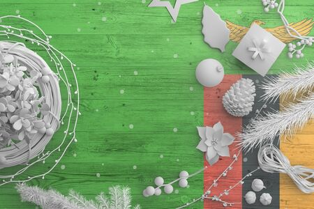 Zambia flag on wooden table with snow objects. Christmas and new year background, celebration national concept with white decor. Foto de archivo