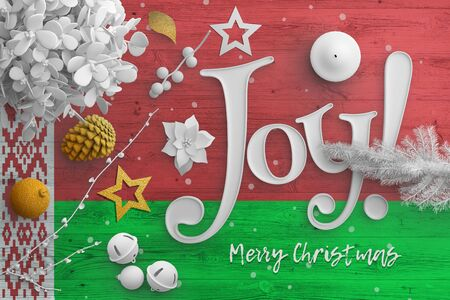 Belarus flag on wooden table with joy text. Christmas and new year background, celebration national concept with white decor.