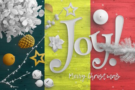 Belgium flag on wooden table with joy text. Christmas and new year background, celebration national concept with white decor.