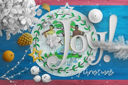 Belize flag on wooden table with joy text. Christmas and new year background, celebration national concept with white decor.