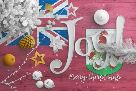 Bermuda flag on wooden table with joy text. Christmas and new year background, celebration national concept with white decor.