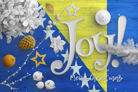 Bosnia Herzegovina flag on wooden table with joy text. Christmas and new year background, celebration national concept with white decor.