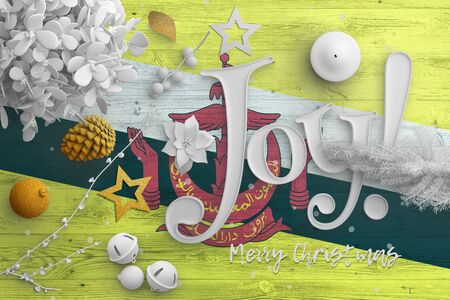Brunei flag on wooden table with joy text. Christmas and new year background, celebration national concept with white decor. Фото со стока
