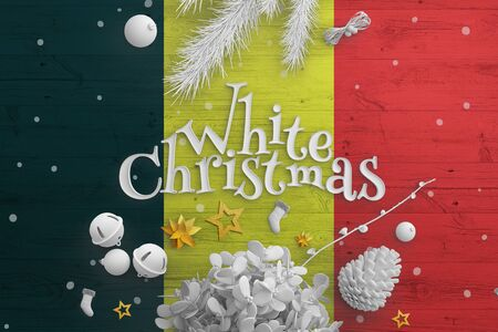 Belgium flag on wooden table with White Christmas text. Christmas and new year background, celebration national concept with white decor.