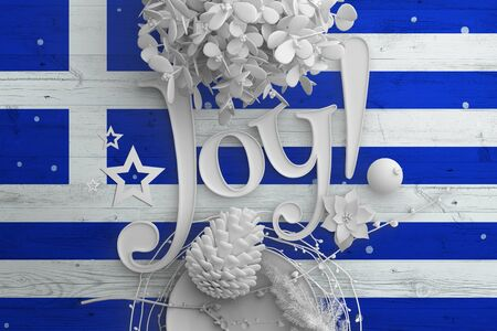 Greece flag on wooden table with Joy text. Christmas and new year background, celebration national concept with white decor. Standard-Bild