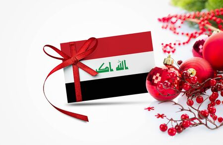 Iraq flag on new year invitation card with red christmas ornaments concept. National happy new year composition.