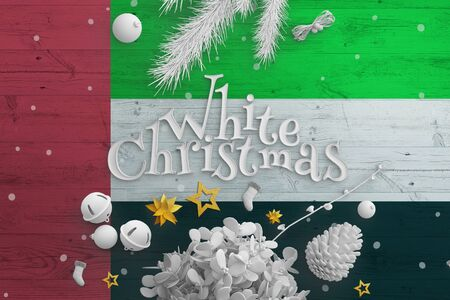 United Arab Emirates flag on wooden table with White Christmas text. Christmas and new year background, celebration national concept with white decor.