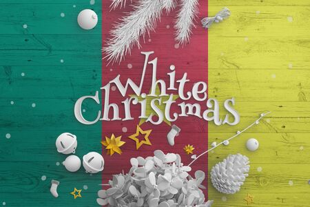 Cameroon flag on wooden table with White Christmas text. Christmas and new year background, celebration national concept with white decor.