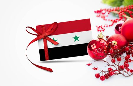 Syria flag on new year invitation card with red christmas ornaments concept. National happy new year composition. Banco de Imagens
