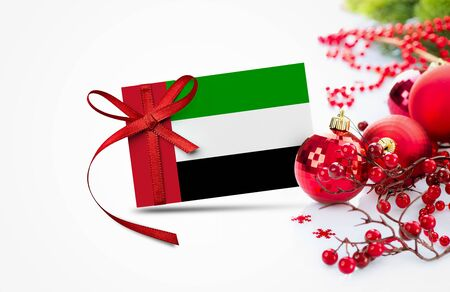 United Arab Emirates flag on new year invitation card with red christmas ornaments concept. National happy new year composition.