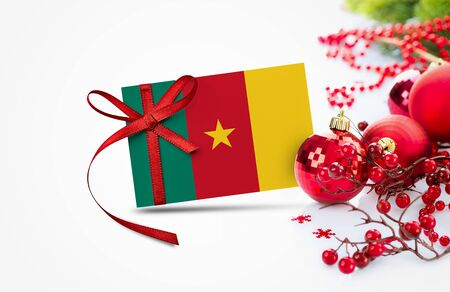 Cameroon flag on new year invitation card with red christmas ornaments concept. National happy new year composition.