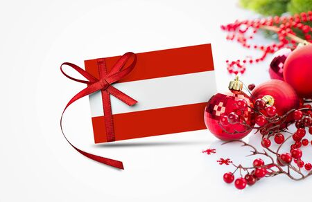 Austria flag on new year invitation card with red christmas ornaments concept. National happy new year composition.