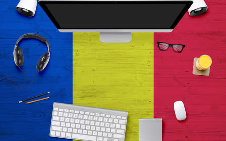 Romania flag background with headphone,computer keyboard and mouse on national office desk table.Top view with copy space.Flat Lay.
