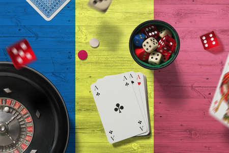 Romania casino theme. Aces in poker game, cards and chips on red table with national flag background. Gambling and betting.