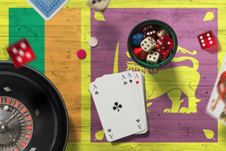 Sri Lanka casino theme. Aces in poker game, cards and chips on red table with national flag background. Gambling and betting.