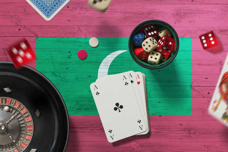 Maldives casino theme. Aces in poker game, cards and chips on red table with national flag background. Gambling and betting. Stockfoto
