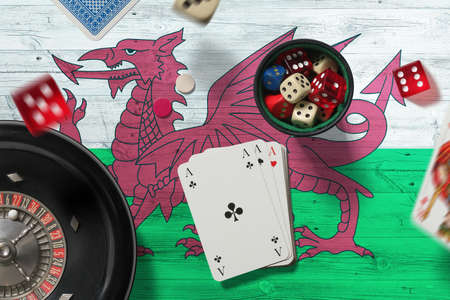 Wales casino theme. Aces in poker game, cards and chips on red table with national flag background. Gambling and betting. Stockfoto