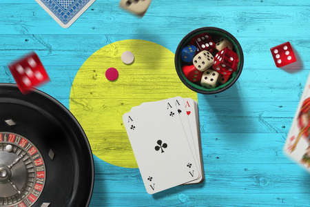 Palau casino theme. Aces in poker game, cards and chips on red table with national flag background. Gambling and betting.