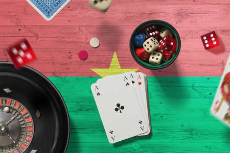 Burkina Faso casino theme. Aces in poker game, cards and chips on red table with national flag background. Gambling and betting. Stockfoto