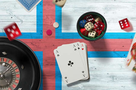 Faroe Islands casino theme. Aces in poker game, cards and chips on red table with national flag background. Gambling and betting. Stockfoto