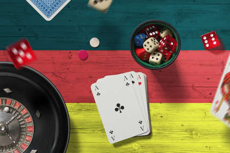 Germany casino theme. Aces in poker game, cards and chips on red table with national flag background. Gambling and betting. Reklamní fotografie