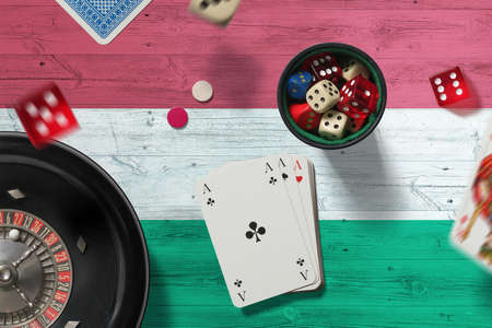 Hungary casino theme. Aces in poker game, cards and chips on red table with national flag background. Gambling and betting.