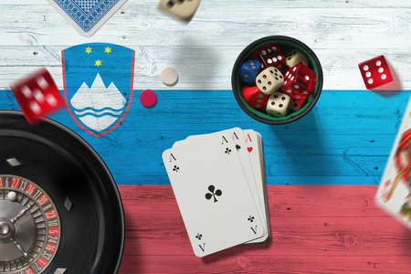 Slovenia casino theme. Aces in poker game, cards and chips on red table with national flag background. Gambling and betting.