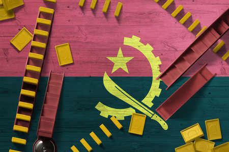 Angola flag with national background with dominoes on wooden table. Top view. Concept of game. Archivio Fotografico