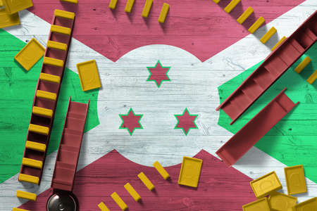 Burundi flag with national background with dominoes on wooden table. Top view. Concept of game.
