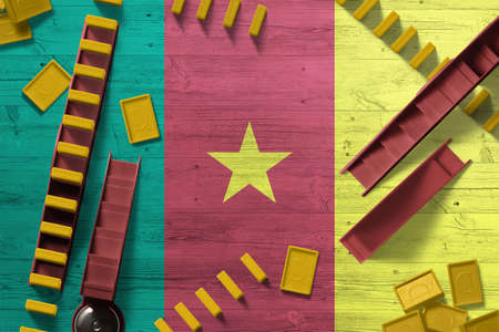 Cameroon flag with national background with dominoes on wooden table. Top view. Concept of game.