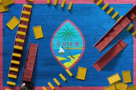 Guam flag with national background with dominoes on wooden table. Top view. Concept of game.