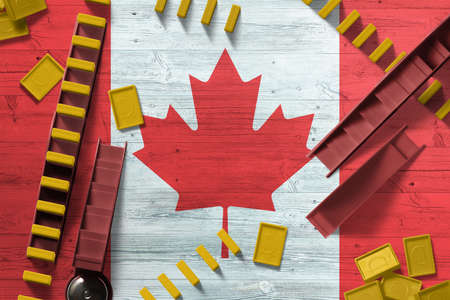 Canada flag with national background with dominoes on wooden table. Top view. Concept of game.