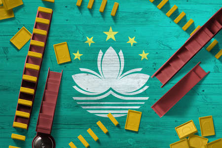 Macao flag with national background with dominoes on wooden table. Top view. Concept of game.
