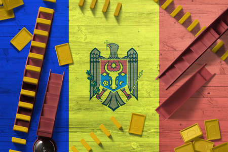 Moldova flag with national background with dominoes on wooden table. Top view. Concept of game. 免版税图像