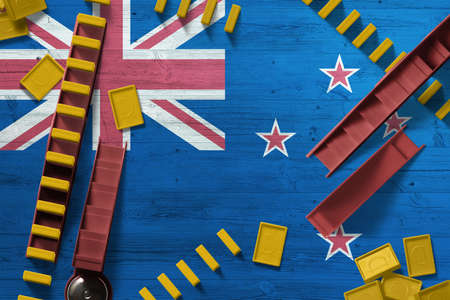 New Zealand flag with national background with dominoes on wooden table. Top view. Concept of game. 免版税图像