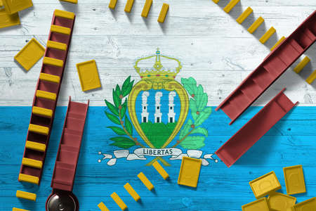 San Marino flag with national background with dominoes on wooden table. Top view. Concept of game.