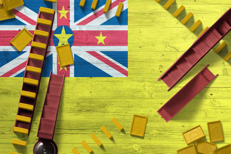 Niue flag with national background with dominoes on wooden table. Top view. Concept of game.